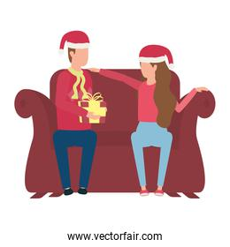 lovers couple with christmas hat and gift seated in sofa