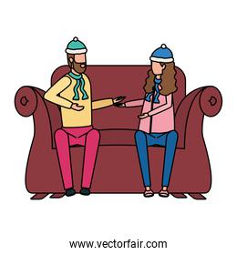 young lovers couple with christmas hat seated in sofa