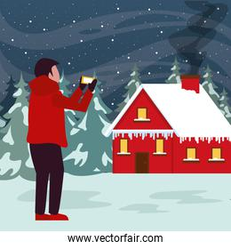 christmas snowscape scene with young boy taking photo