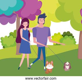 young couple walking with their little dogs in the park