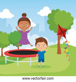 little children in park landscape with trampoline jumping and kite