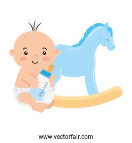 cute baby boy with bottle milk and wooden horse toy