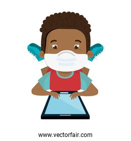 boy using face mask with tablet studying online