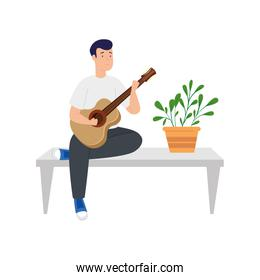 young man stay at home playing guitar in table