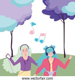 young women in the park with devices and earphones listening music