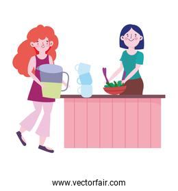 people cooking, woman and girl with juice jar vegetables in bowl counter kitchen