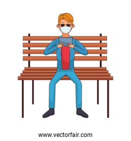 young man using medical mask and tablet in park chair