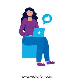 young woman using laptop seated in chair
