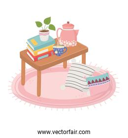 sweet home table with stack of books, potted plant and tea cup