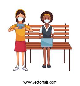 interracial women wearing medical masks using technology seated in park chair
