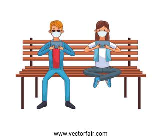 young couple wearing medical mask using technology seated in park chair