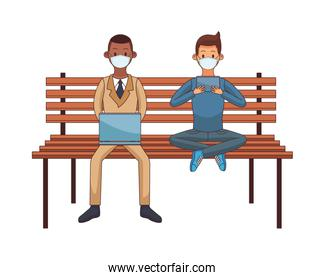 interracial men wearing medical masks using technology seated in park chair