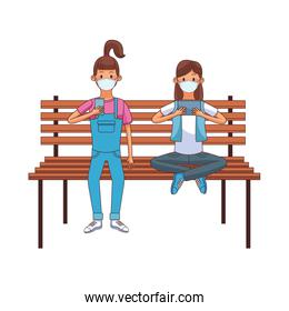 young women wearing medical masks using technology seated in park chair
