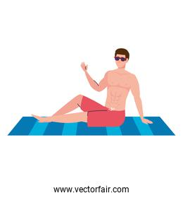 man in shorts, happy guy in swimsuit sitting on the towel