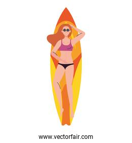 woman with swimsuit, lying down on surfboard, summer vacation season
