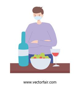 restaurant social distancing, man with medical mask alone with food, covid 19 pandemic, prevention of coronavirus infection