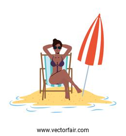 afro woman relaxing on the beach seated in chair and umbrella