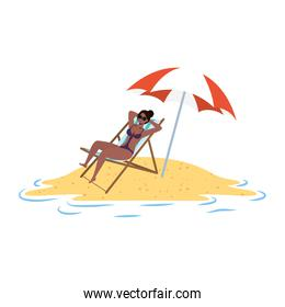 young afro woman relaxing on the beach seated in chair and umbrella