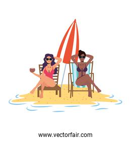 interracial girls relaxing on the beach seated in chairs and umbrella