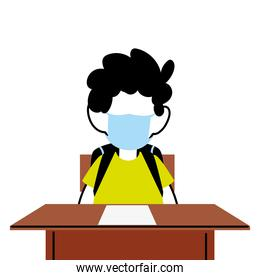 boy with face mask at school desk