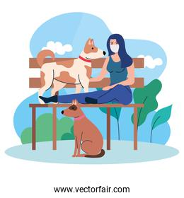 woman wearing medical mask, sitting in park chair with dogs pets