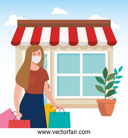 happy woman wearing medical mask, carrying shopping bags, with facade shop