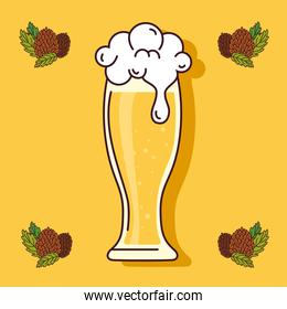 glass of beer with seeds hop on yellow background