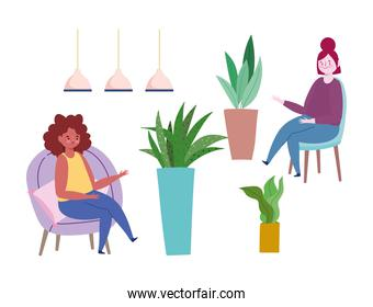 women sitting on chairs potted plants and lamps decoration