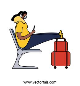 afro young woman wearing medical mask with suitcase in waitingroom