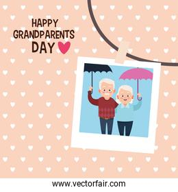 happy grandparents day card with old couple lifting umbrellas in photo