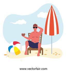 man wearing swimsuit seated in beach chair eating coconut