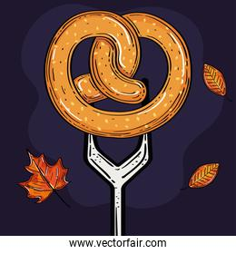 appetizing pretzel in fork, with autumn leaves decoration