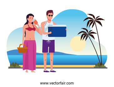 young couple wearing swimsuits with cocktail and fridge box on the beach