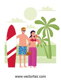 young couple wearing swimsuits with cocktail and surfboard on the beach
