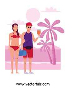 young couple wearing swimsuits drinking cocktails on the beach