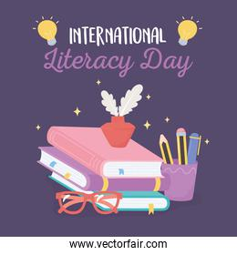 international literacy day, ink and feather on books glasses and pencils