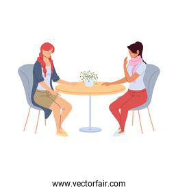 young women smiling and talking in restaurant