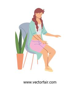 Young woman sitting on a chair nect to a flower pot