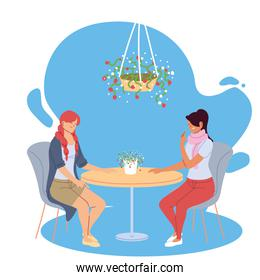 young women smiling and talking in a beautiful restaurant