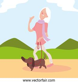 old woman walks a dog in park, active senior