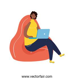 afro ethnic woman working in laptop seated in sofa