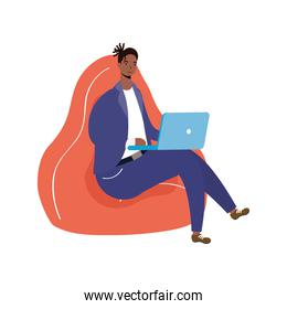 afro ethnic man using laptop seated in sofa character