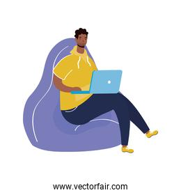 afro ethnic man with beard using laptop seated in lilac sofa