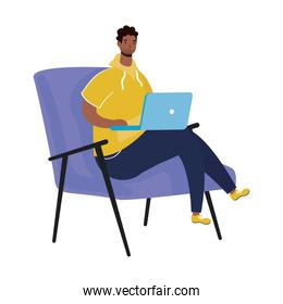 afro ethnic man with beard using laptop seated in sofa