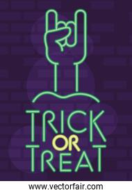 trick or treat halloween lettering in neon light with hand rock and roll symbol