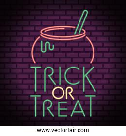 trick or treat halloween lettering in neon light with cauldron
