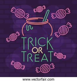 trick or treat halloween lettering in neon light with cauldron and candies