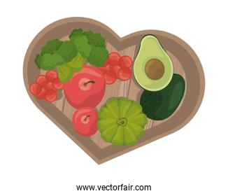 tomatoes and vegetables in wooden kitchen board with heart shape