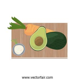 half avocados and carrot in   kitchen board