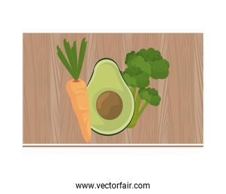 half avocado and carrot in wooden kitchen board